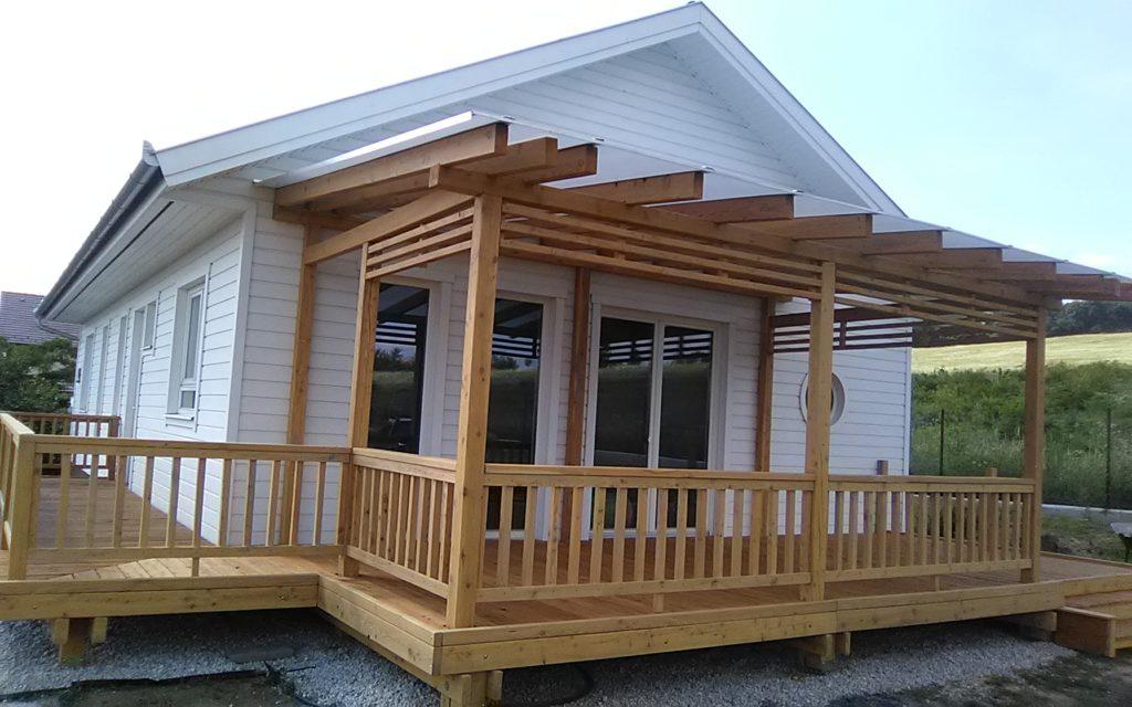 Könnyűszerkezetes faházhoz épült polikarbonát előtető vörösfenyő terasszal